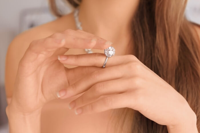 woman-wearing-an-engagement-ring-with-heavy-top-settings