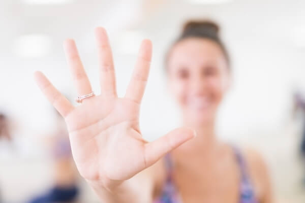 women-showing-her-hands-with-ring-in-yoga-studio
