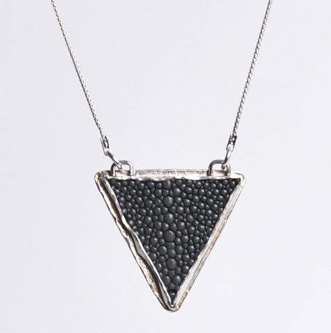 A black, bumpy equilateral triangle hangs from a silver chain pointing downwards.  The triangle has a silver metal edge with two loops where the chain attaches.