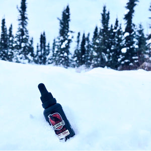 Full spectrum CBD sublingual drops from Alaskan brand Red Raven CBD displayed in the Alaskan snow in front of an evergreen forest.