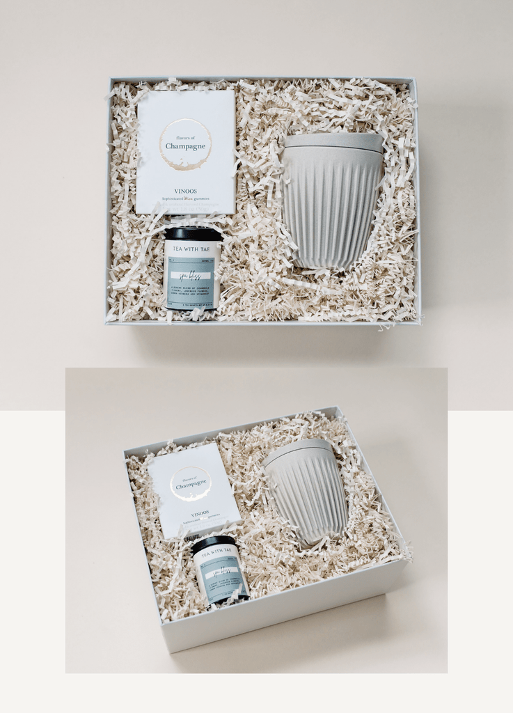 Open elegant curated gift box with wine flavored gummies, relaxing tea, and eco friendly reusable mug.