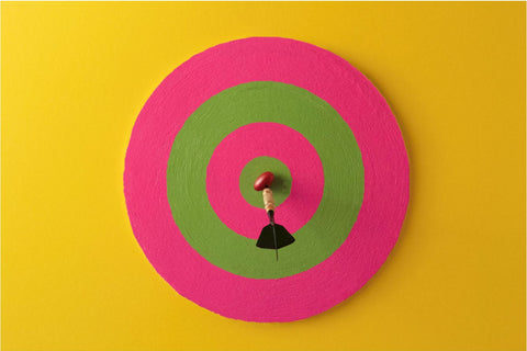 Pink and green dartboard with a red berry held up in the center of the dart board by a black and gold dart. All against a bright yellow background.