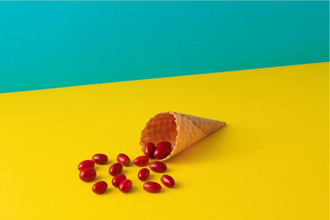 Red berries spilling out of an ice cream cone laying on its side. Foreground is bright yellow, background is bright teal.