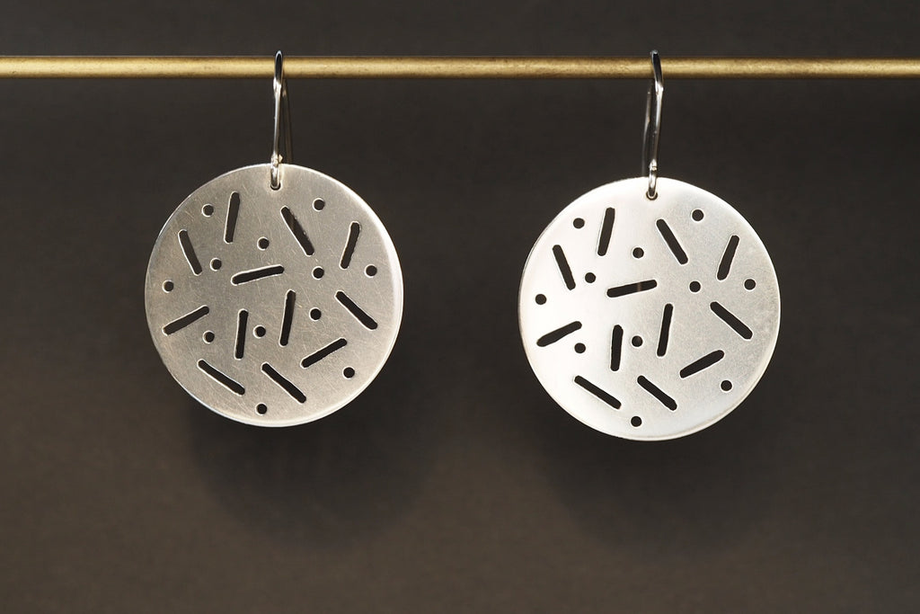 Round polished earrings with cut out pattern on hooks.  Materials: Sterling Silver  Dimensions: 4 x 2.8cm