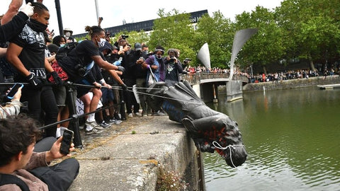 A Bristol, UK statue of slave trader Edward Colston is rolled into the harbour by Black Lives Matter protestors in June