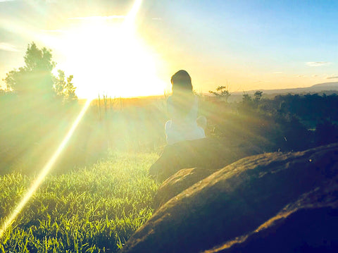 Claire Chitham sits on a rock at Gaia Retreat in Australia