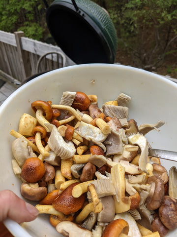 Chopped mushrooms. Shiitake, Oyster, Lions Mane in a mixing bowl. Big Green Egg in the background.
