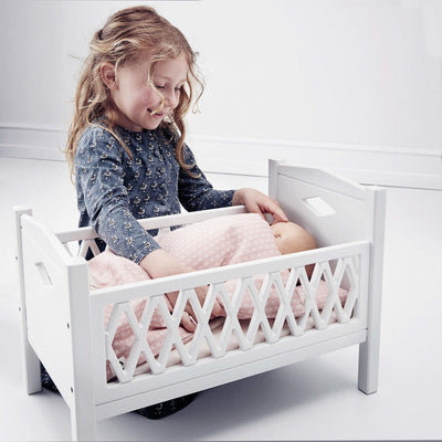 Child playing with Cam Cam Copenhagen Harlequin Doll's Cot & Bedding