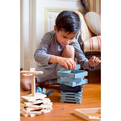 Child building structure using KAPLA blue and navy colour wooden building planks