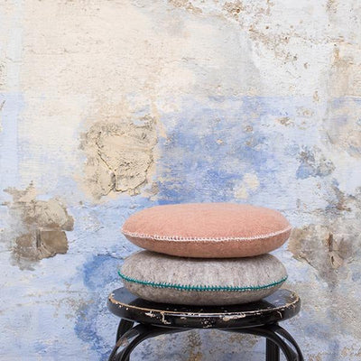 Stack of pink and grey Muskhane round wool Smartie cushions on a stool
