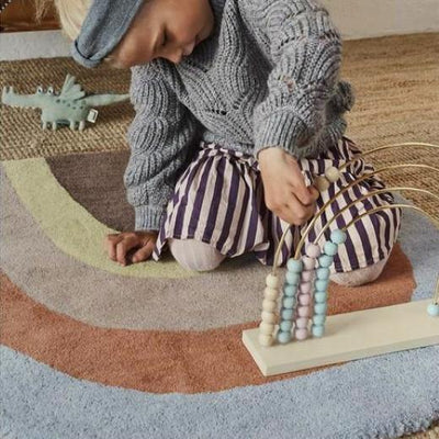 OYOY | Wooden Toy | Rainbow Abacus | girl playing on rainbow rug
