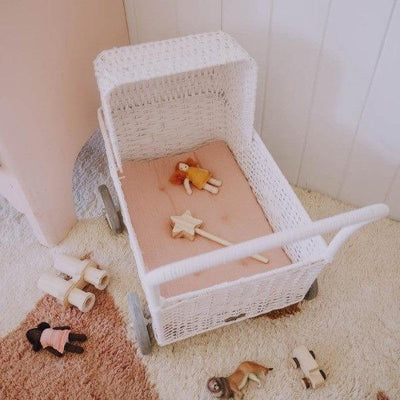 Olli Ella Strolley in White Rattan styled with Rose Pink Mattress and Toys