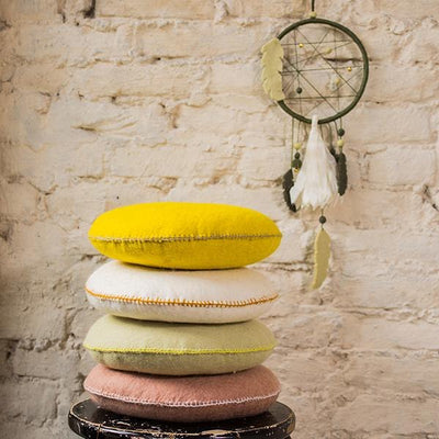 Stack of Muskhane round wool Smartie cushions