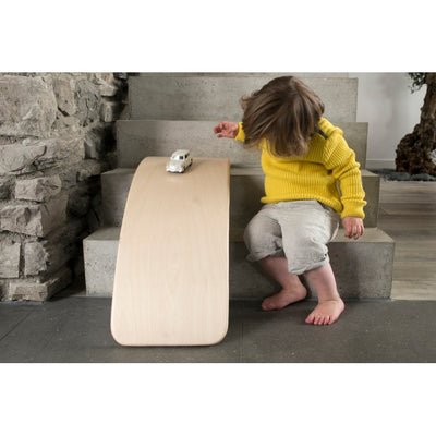 Child using Wobbel Board as a bridge for cars