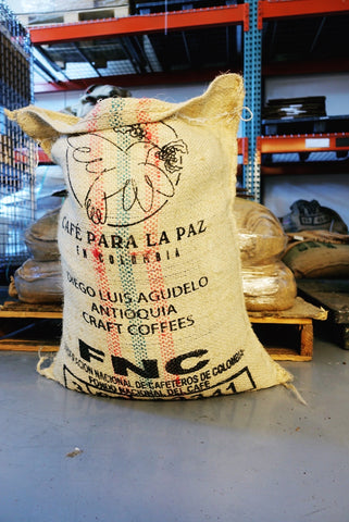 woodcat coffee: large burlap bag of green coffee with the letters FNC printed in black on the outside
