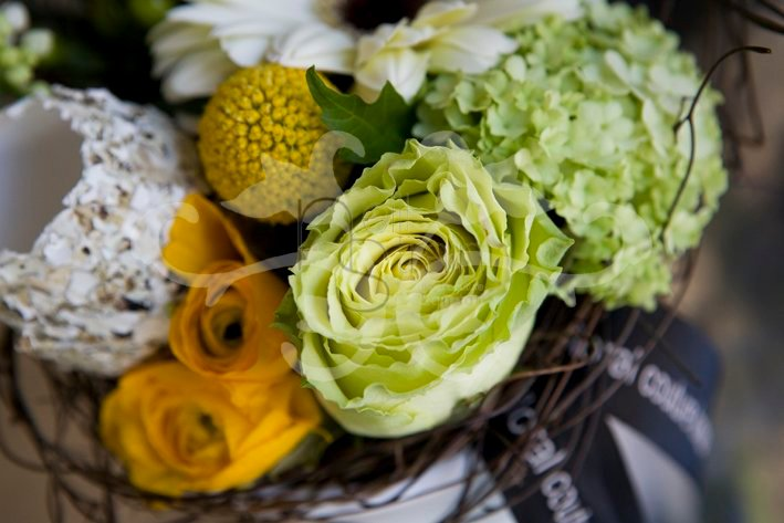 Easter floral arrangement in a container with Roses, Viburnum Opulus, Craspedia, twigs and accessories.