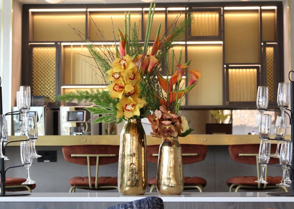 Cymbidium and Vanda Orchids with Calla Lilies and Heliconia pick up the colour palette and modern, linear style of the first floor bar