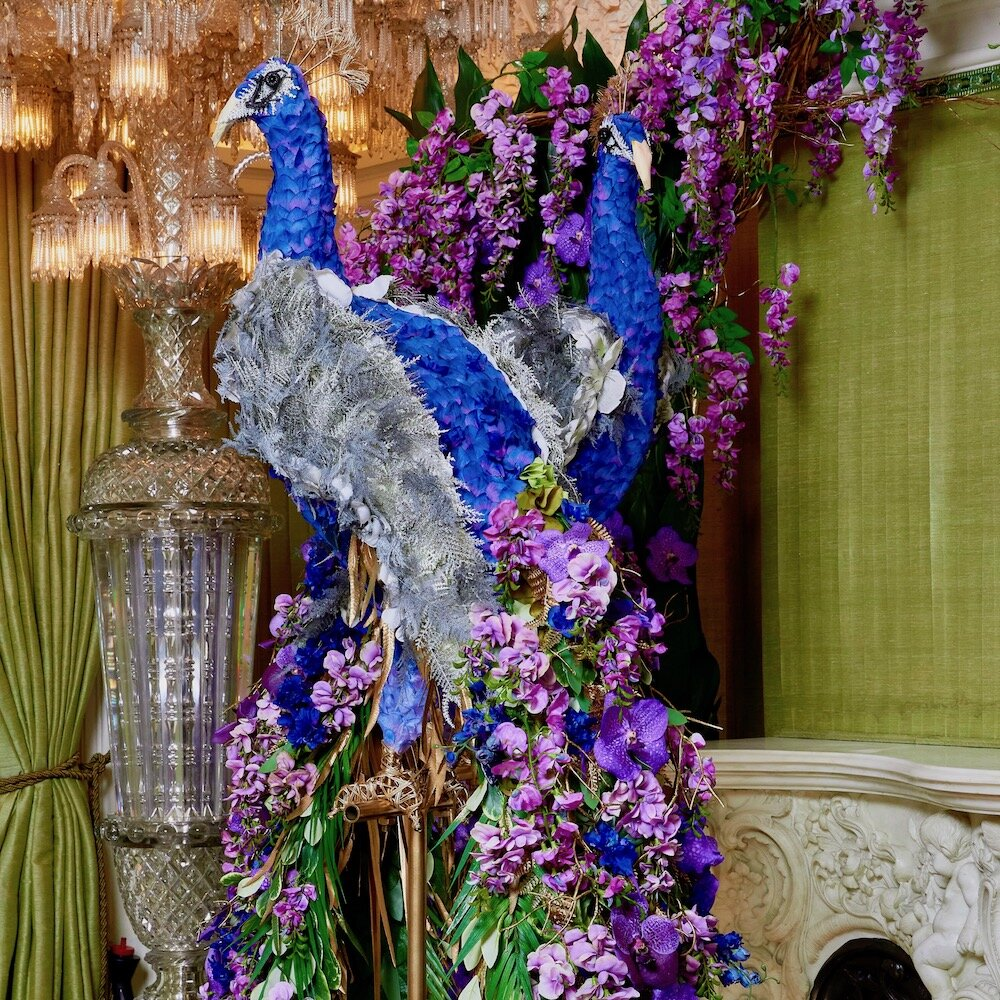 Peacocks created entirely with fresh and faux flowers and plant material on a wired frame