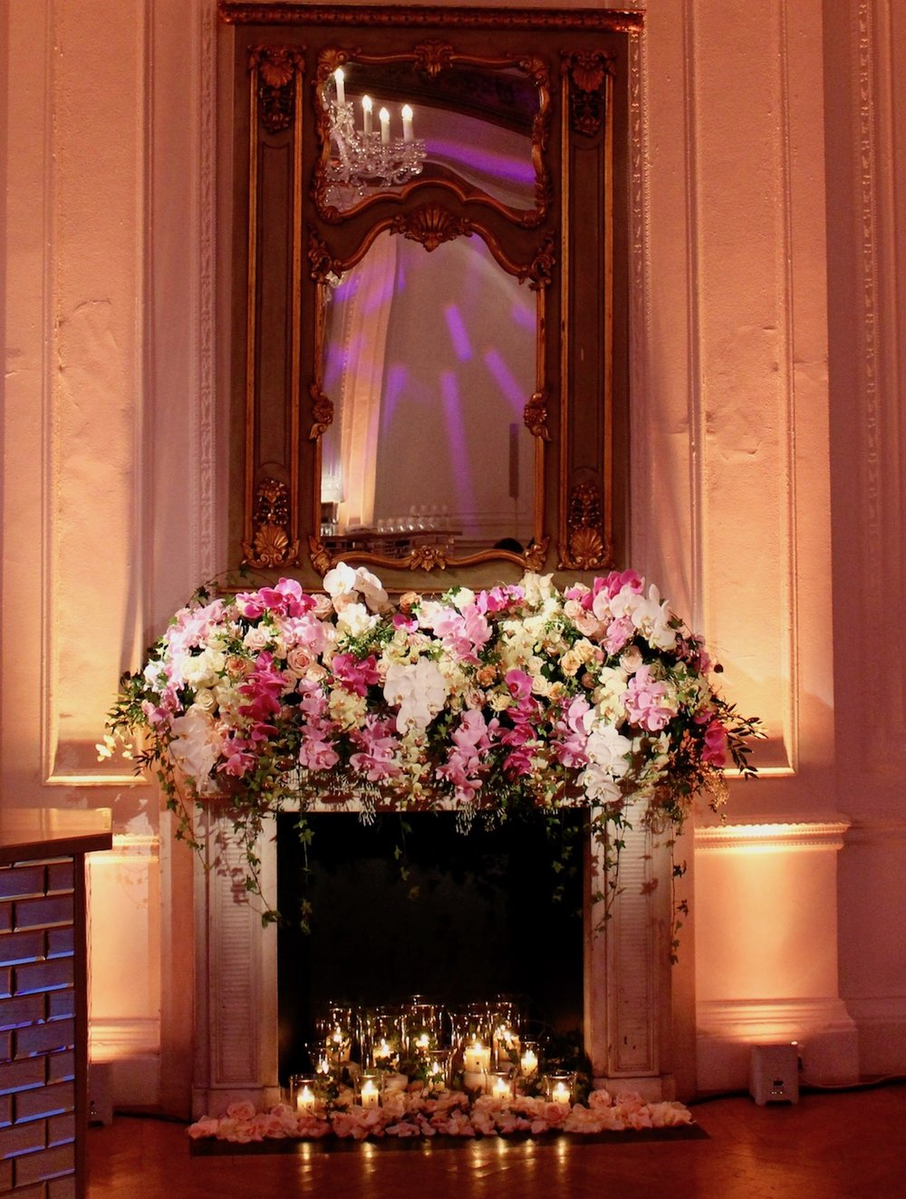 Fireplace adorned with Roses and Orchids by Neill Strain Floral Couture
