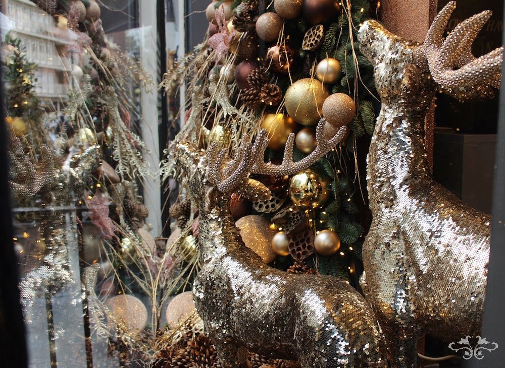 Small and medium sized golden reindeers displayed in the window at Neill Strain Floral Couture. Also available in a larger, taller size.