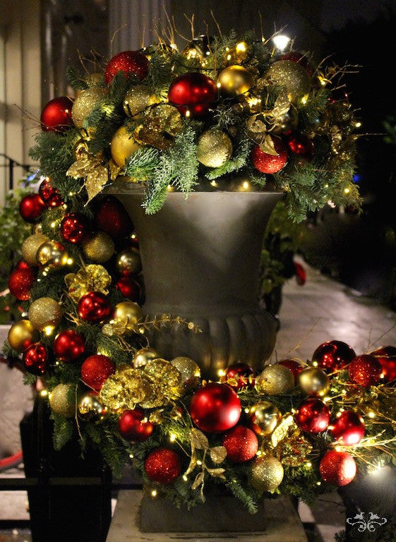 Medici urns ladened with Christmas foliage,baubles and gold Phalaenopsis Orchids. Baroque opulence revival.