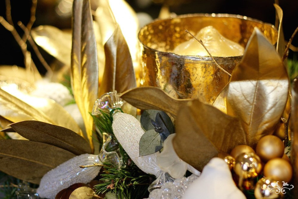 Christmas wreath with gold Magnolia leaves, crystal sweets and baubles with a gold glass candle container
