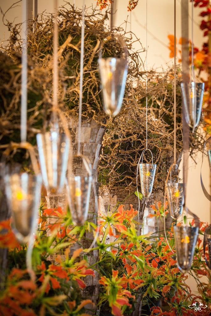 Tall vases covered with squares of Birch bark and topped with spheres of moss and gold Orchid roots dominate the table.