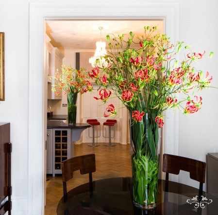Tall glass vase arrangement with foliage and 1 m stems of Gloriosa