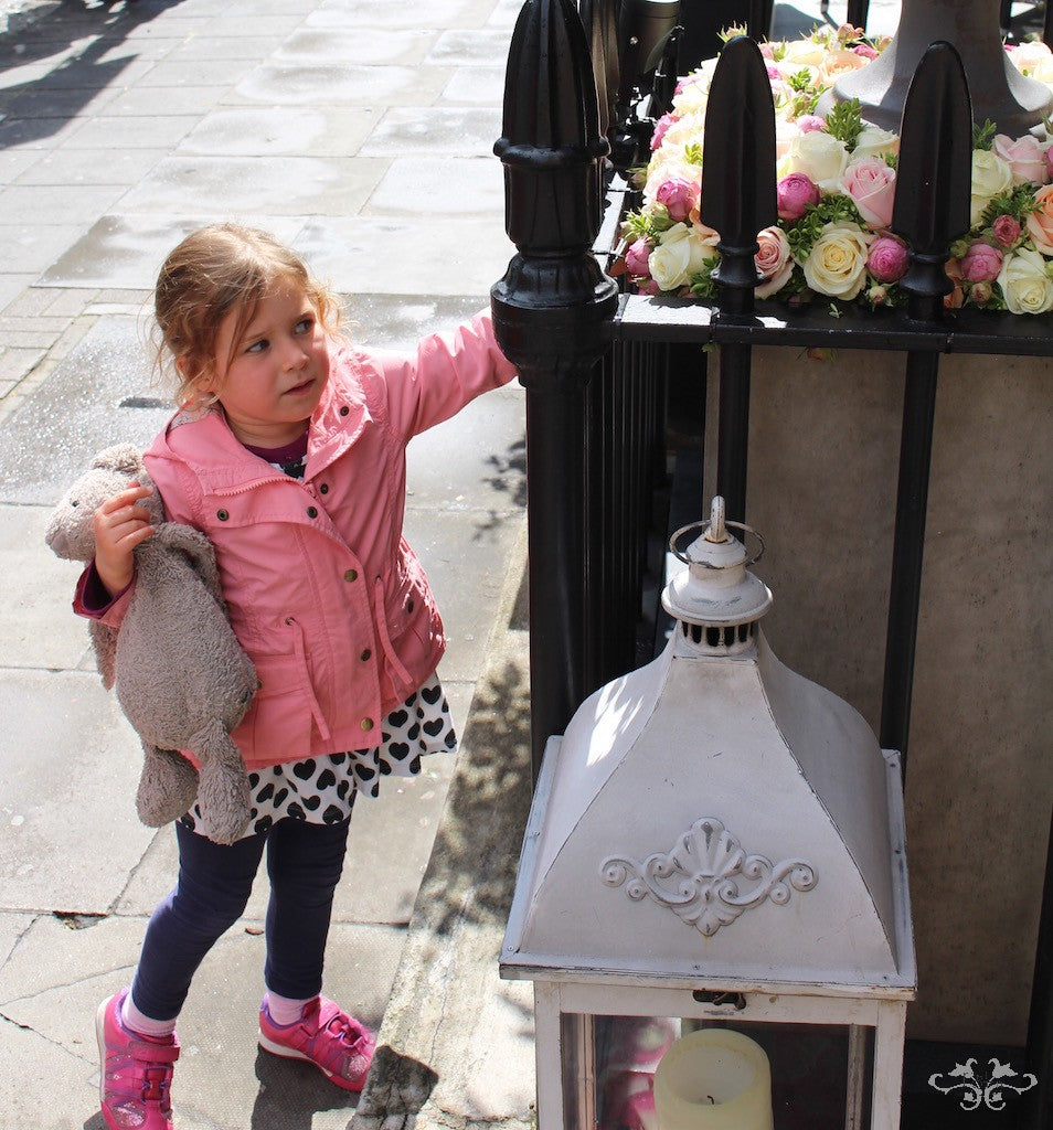 A child passing by reaches out to touch the Roses to check if they are real or not!