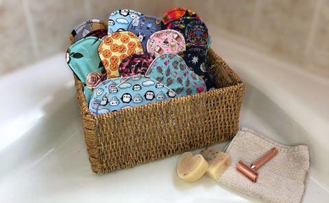 wicker basket with a variety of pretty colourful reusable pads alongside a washcloth, a rose gold razor and handmade soap