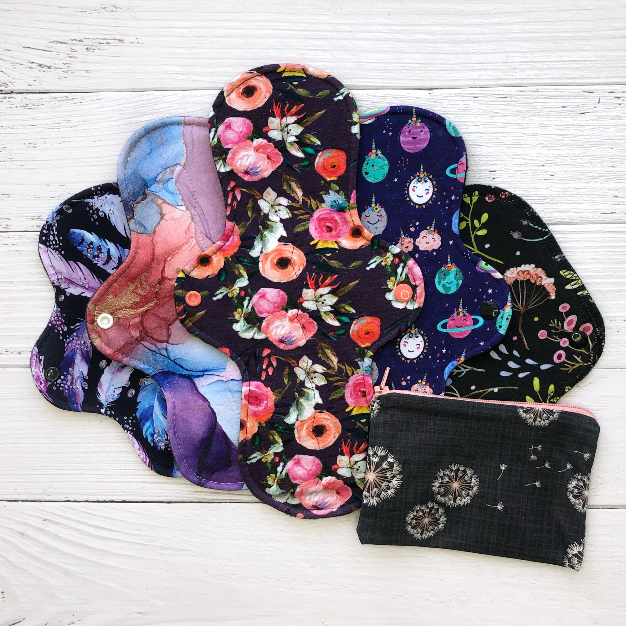 basic reusable pad starter set with 5 colourful reusable pads in floral and other prints and a dandelion print small wetbag