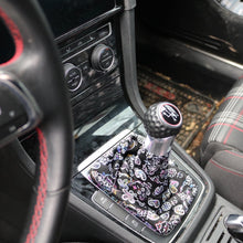 "Load image into Gallery viewer, Love to Shift ""Black Paisley Brights"" custom shift boot cover for a manual car shown in a VW GTI from an above side angle."