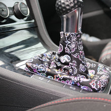 "Load image into Gallery viewer, Love to Shift ""Black Paisley Brights"" custom shift boot cover for a manual car shown in a VW GTI from a side angle."