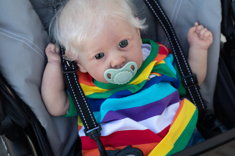 Saskia sculpt sitting in a stroller, wearing a rainbow shirt with a green pacifier in her mouth,