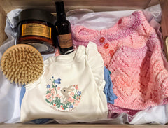 Product image of new mum gift, showing baby clothes and pamper items
