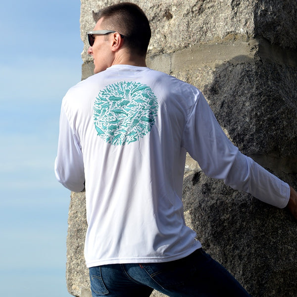 young man climbing seawall in white performance fishing shirt by Hook Life
