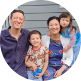Family photo of a caucasian male and asian female with two young children smiling
