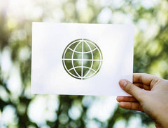 environmentally friendly lifestyle picture showing a white cardboard cut out of planet earth with gaps where the green woodland background can be seen clearly.