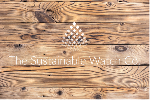 the sustainable watch company logo in white set on a background of natural light wood planks