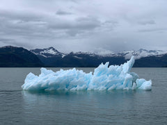A cloudy landscape containing melting glacier set in the middle of a cold lake against a background of snow tipped mountains. This image depicts global warming and climate change and the importance of sustainability.