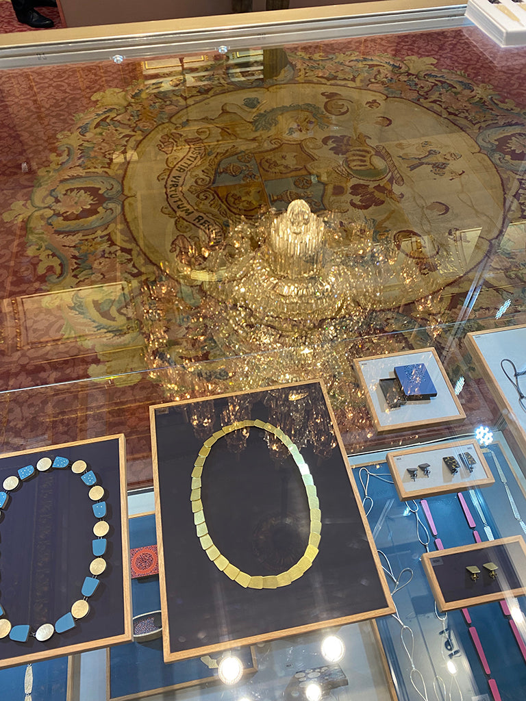 A photo looking down through the cabinet with the chandelier reflected in the glass