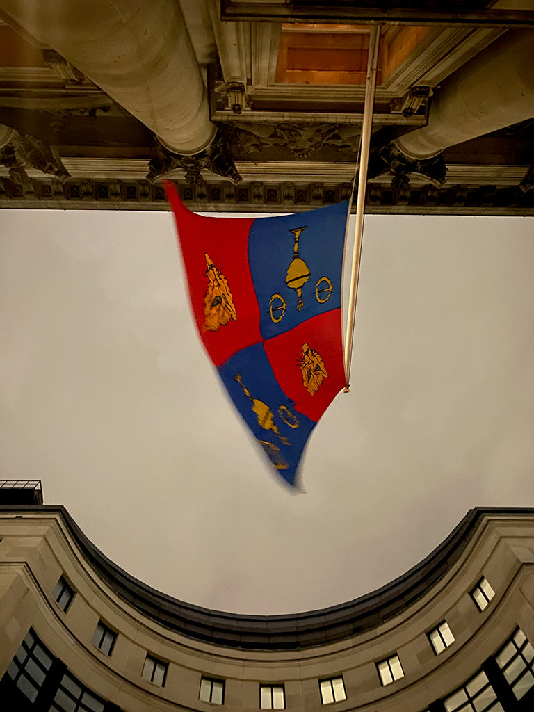 Stepping out of Goldsmiths' Hall and looking up, a photograph showing the Goldsmiths' Company flag against the evening sky.