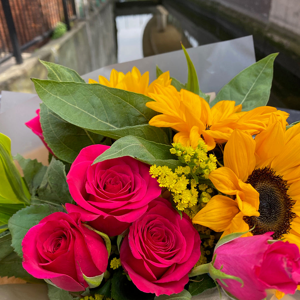 a bunch of sunflowers and pink roses