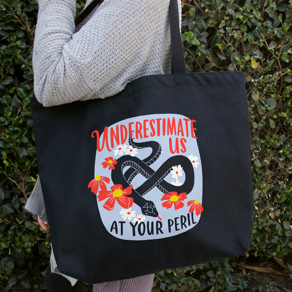 Person holding Underestimate Us Tote