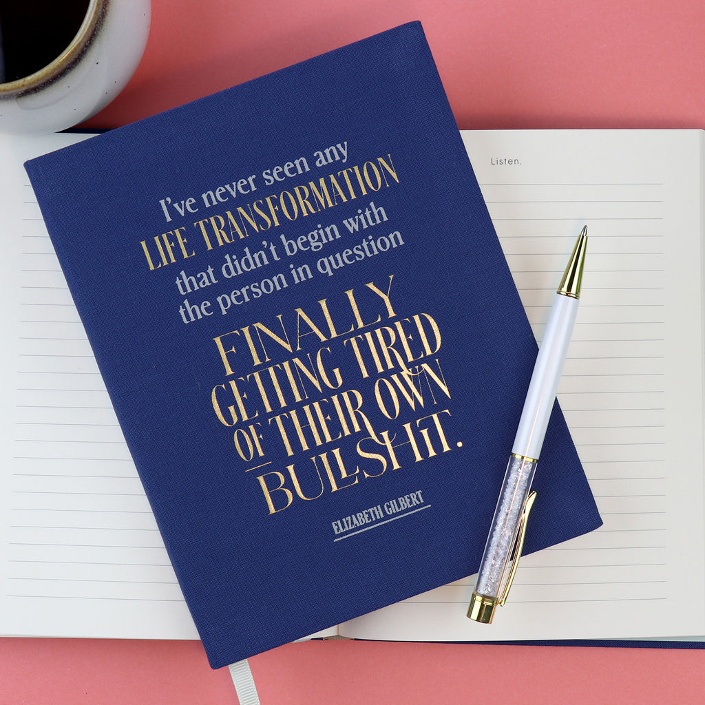 Transformation Elizabeth Gilbert Journal atop other journal with a pen