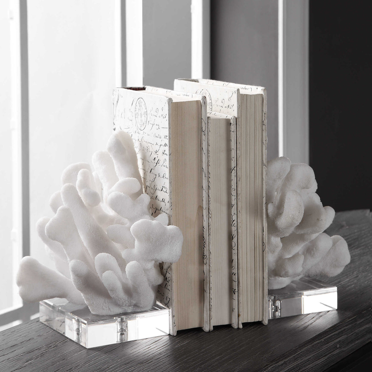 Set of two bookends featuring textured faux white coral on crystal bases. Sizes: S-5x9x8, L-6x9x8