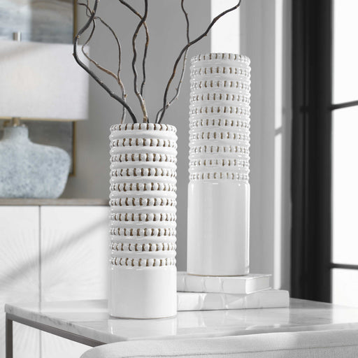 Set of two ceramic vases finished in a white glaze with taupe accents, beaded texture, and a ribbed interior. Sizes: Sm-5x14x5, Lg-5x18x5