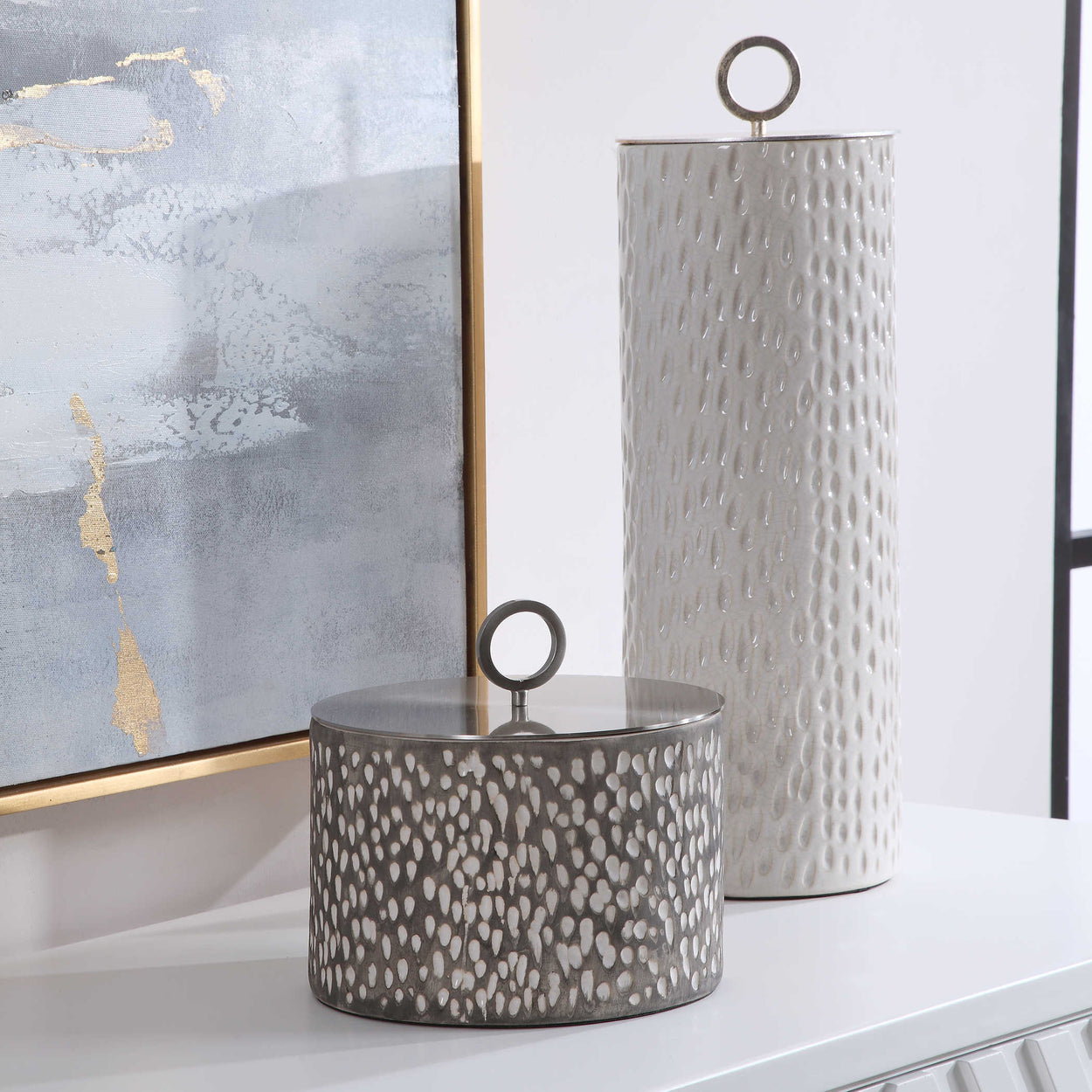 Ceramic containers feature carved detailing and are finished in off-white and smoke gray crackle glazes with respective aged gold and brushed nickel finished lids. Sizes: S-9x9x9, L-6x19x6