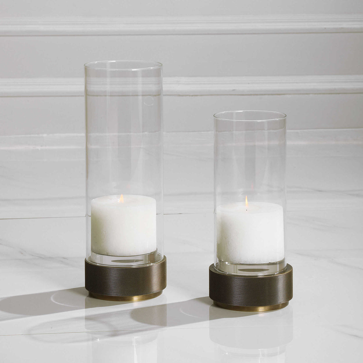 Sophisticated and traditional, these candleholders feature an iron base finished in antique brushed brass, accented by crystal details and a clear glass hurricane. Sizes: S-5x11x5, L-5x14x5