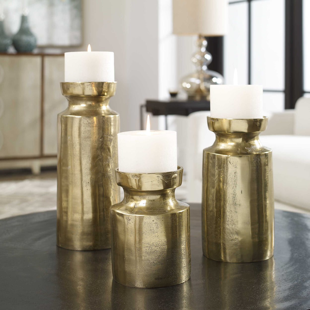"Set of three, textured cast aluminum candleholders feature an antiqued brass finish and completed with three 4""x 4"" white candles. Sizes: Sm-5x7x5, Med-5x10x5, Lg-5x13x5"